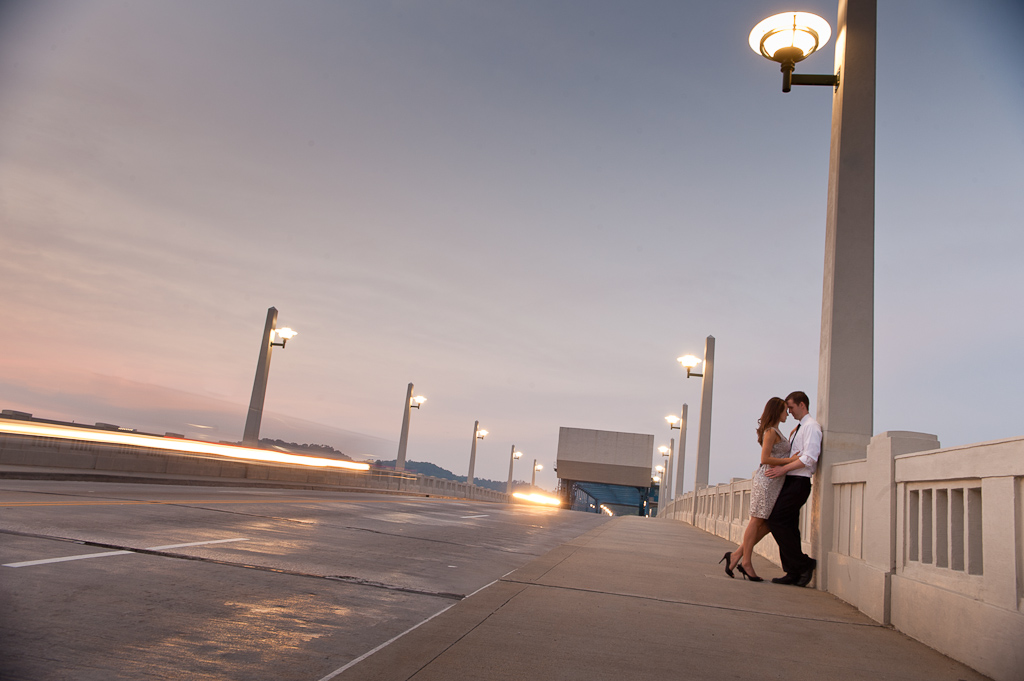 An engaged couple embrace at twilight on the Market Street bridge in Chattanooga, TN.